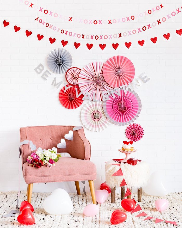 be my valentine banner, hearts garland hanging on white wall, pink armchair, valentines day decor, heart shaped balloons on the floor