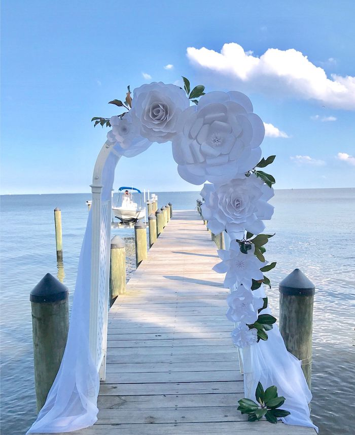 wooden arch, decorated with white tulle, large white paper roses, placed on a wooden pier, paper flower templates