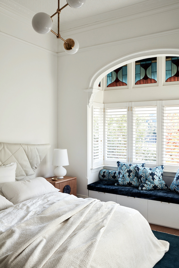 bedroom with white walls, large windows with blinds, stained glass panels, bench with blue velvet pillows