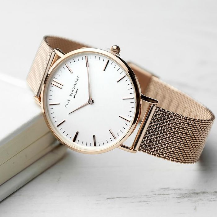 valentines gifts for her, rose gold watch, leaning on a book, placed on white surface