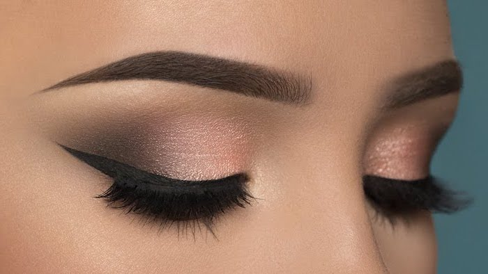 rose gold smokey eye, black cat eyeliner, blue eyeshadow, woman with dark thick eyebrows