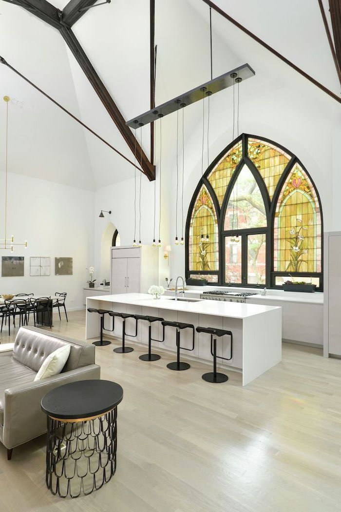 kitchen with white kitchen island and black stools, stained glass windows, cathedral ceiling and window, wooden floor