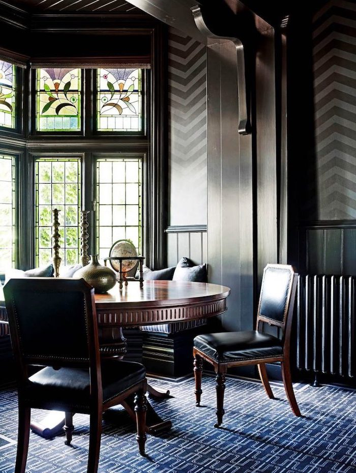 massive round wooden table, black leather chairs, how to make stained glass, dark walls and blue carpet, large windows