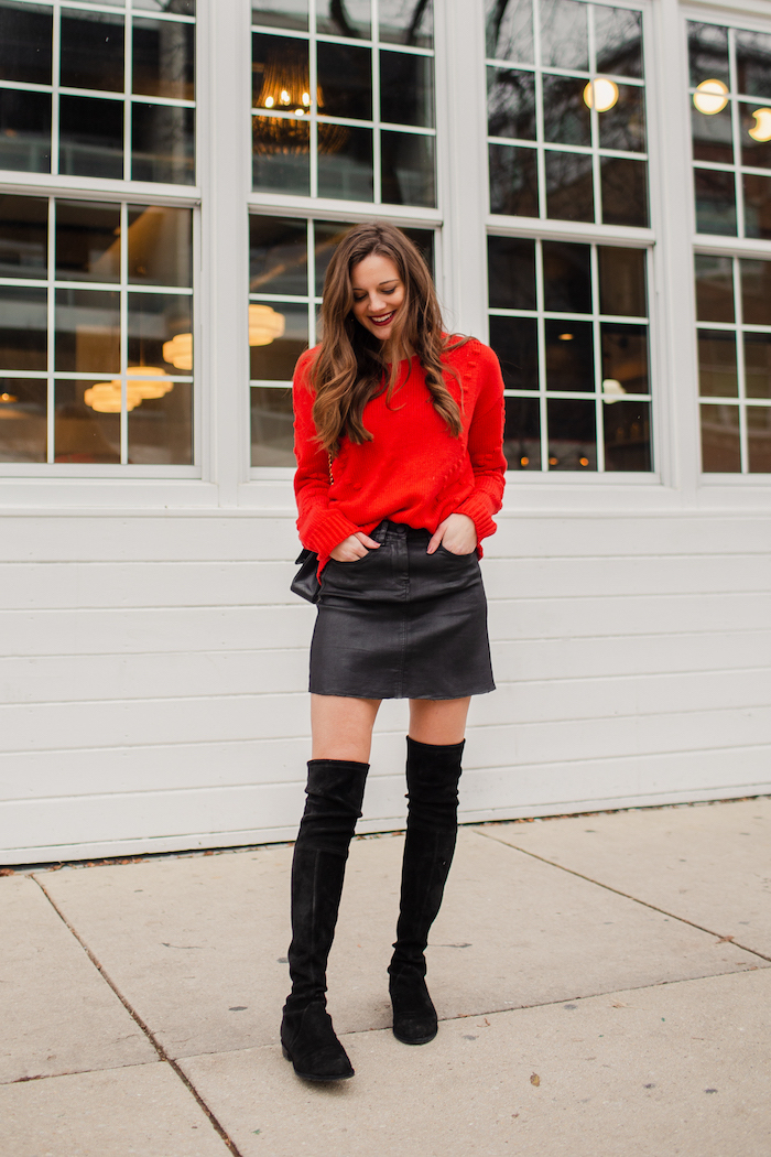woman wearing red blouse, valentines day outfits, black leather skirt, black velvet knee high boots, standing on sidewalk