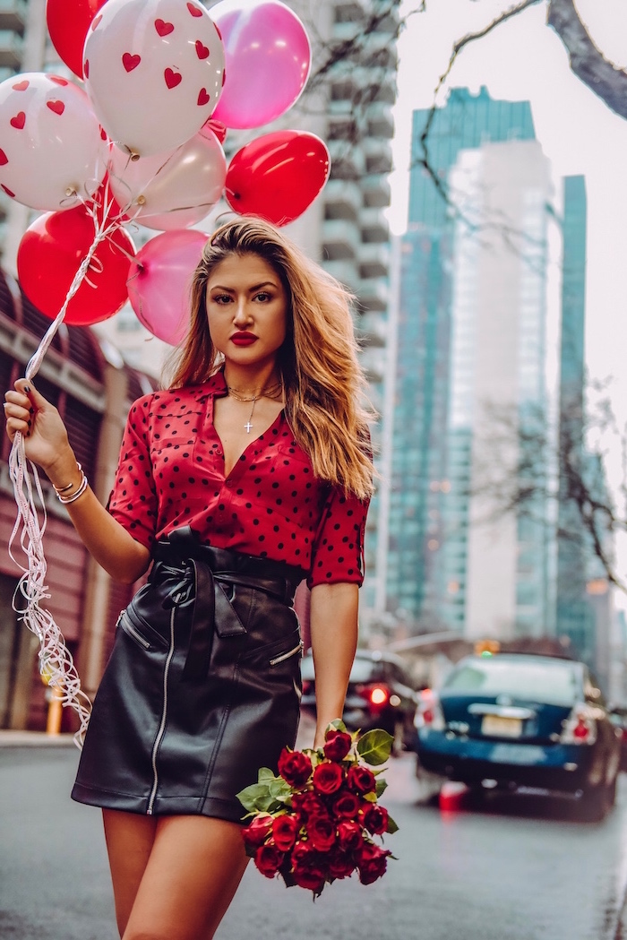 woman holding a bunch of balloons, valentines day outfits, wearing black leather skirt, red blouse with black polka dots