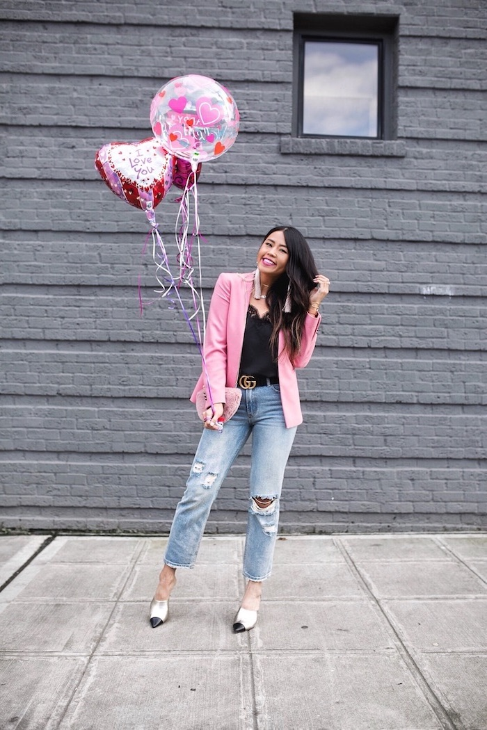 woman holding a bunch of balloons, valentines day dresses, wearing black top and jeans, pink blazer