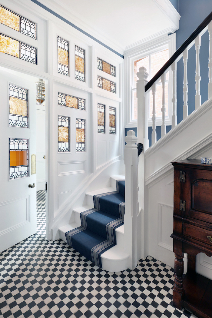 white staircase with blue carpet, stained glass panels, white and black tiled floor, large door with decorated windows