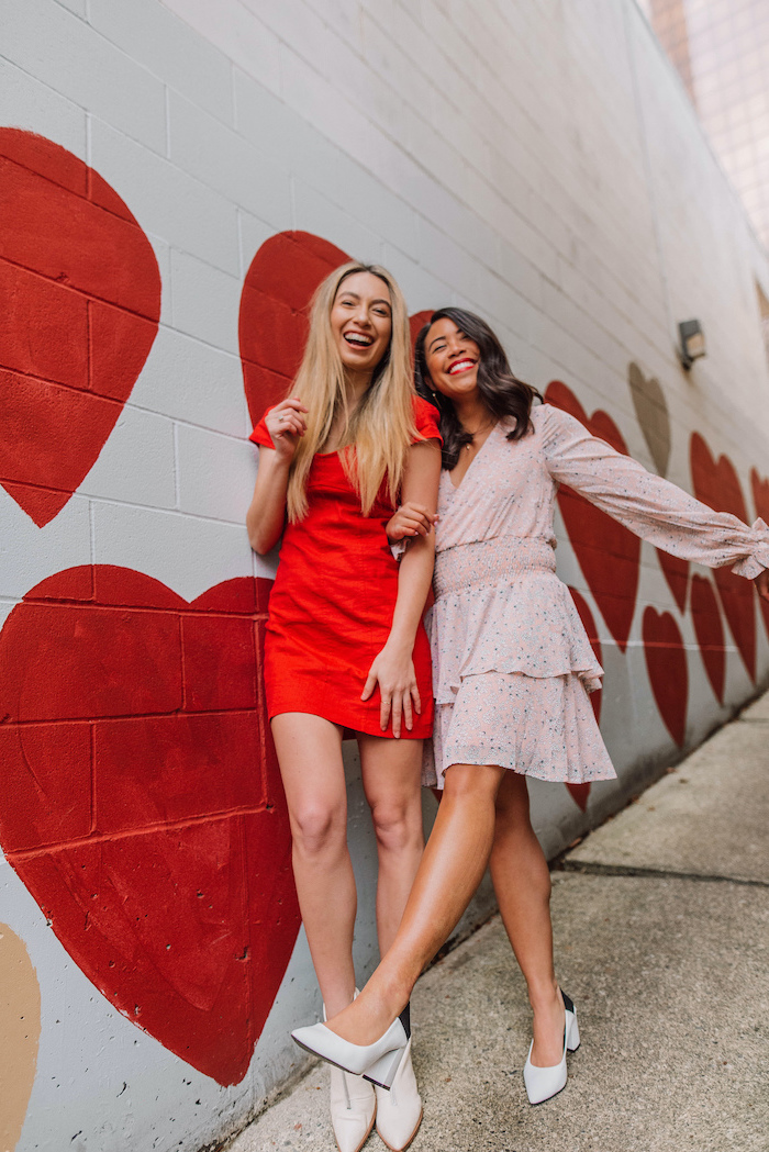 two women laughing, leaning on white wall, hearts drawn on it, valentines day dresses, wearing red and pink dresses
