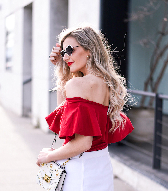 blonde woman wearing red open shoulder crop top, white short skirt, valentines day dresses, heart shaped glasses