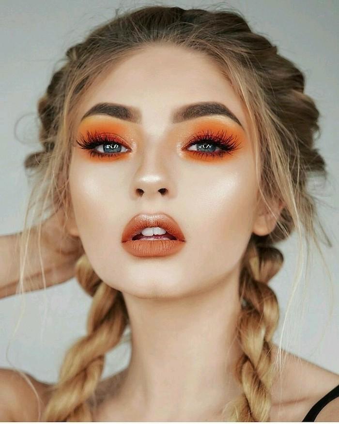 blonde woman with two braids, blue eyeshadow, orange eyeshadow color, dark brown matte lipstick