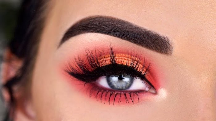 woman with blue eyes, dark thick eyebrows, orange and red eyeshadow colors, black cat eyeliner, eyeshadow tutorial