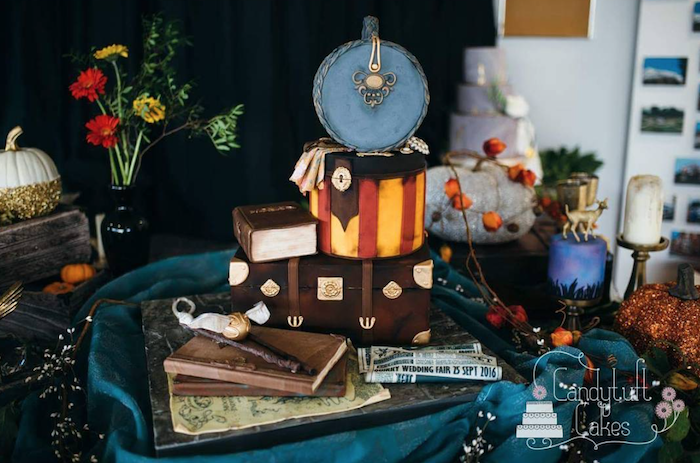 large cake with multiple different layers, shaped as trunks and books, arranged on large tray, happee birthdae harry