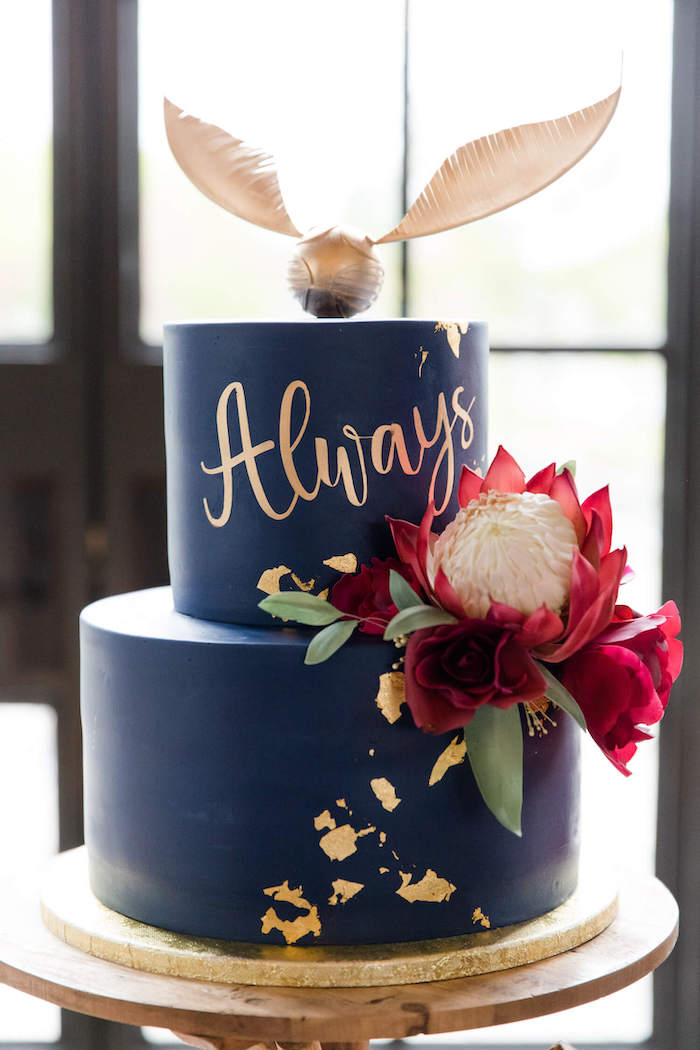 two tier cake, covered with blue fondant, golden snitch topper, happee birthdae harry, large flower on the side