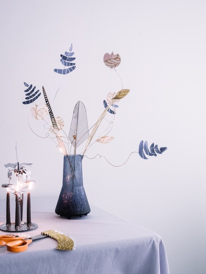 diy paper flowers, blue vase, placed on a table, filled with paper flowers threaded with a wire, white background