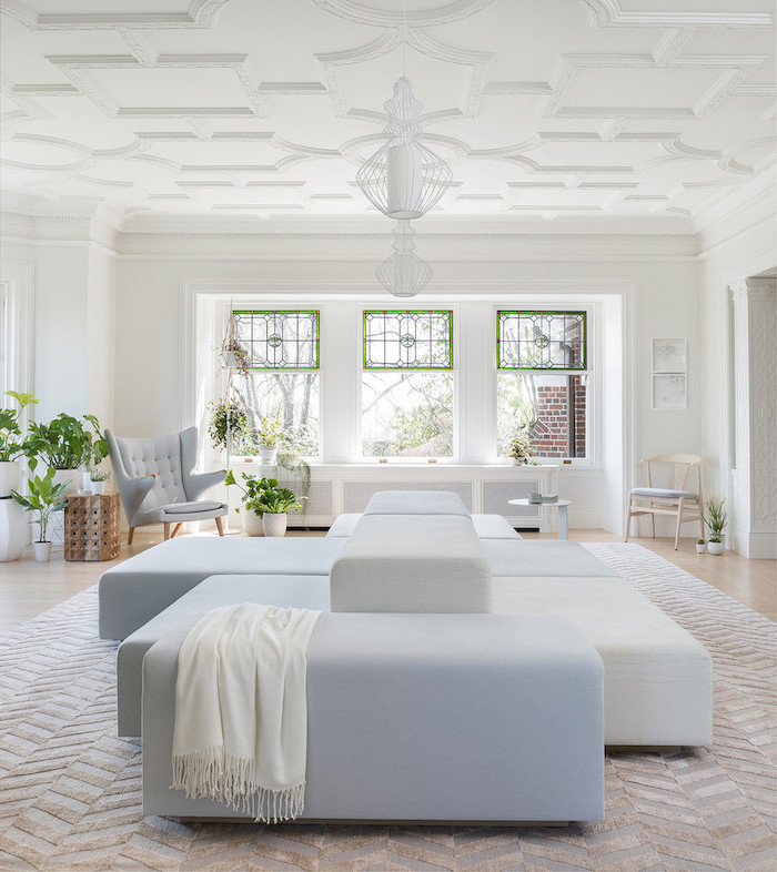 blue and white large sofa, in the middle of a living room with white walls, large windows, how to make stained glass
