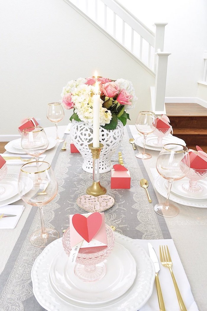dinner table with candles, heart decorations, flower bouquet in the middle, pink heart boxes inside glasses