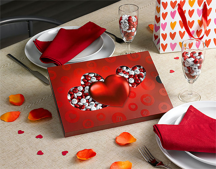 box of red and white m and ms, valentines gifts for her, placed on a table with dinner plates, red napkins in the plates