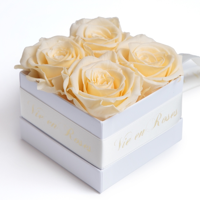 valentines day ideas for her, four white roses inside white square box, white satin bow around it, vie en roses