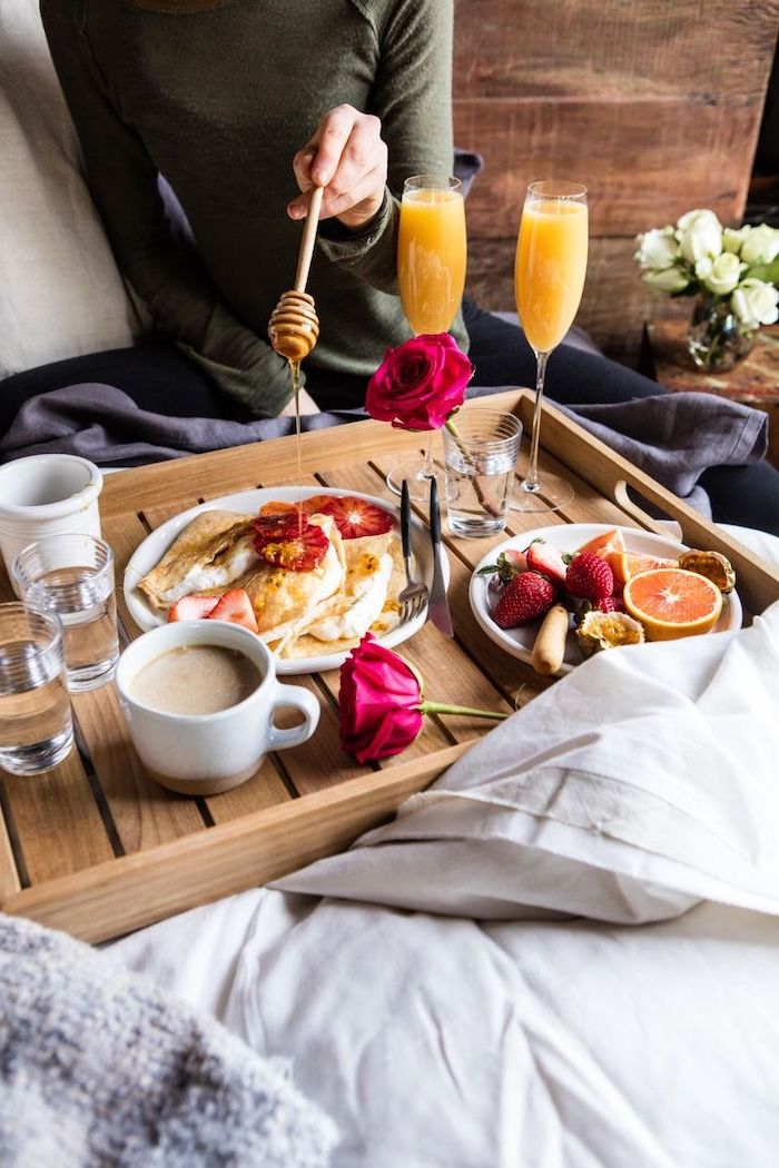 breakfast in bed, served on wooden tray, valentines day ideas for her, pancakes and fruits in white plates, orange juice and coffee