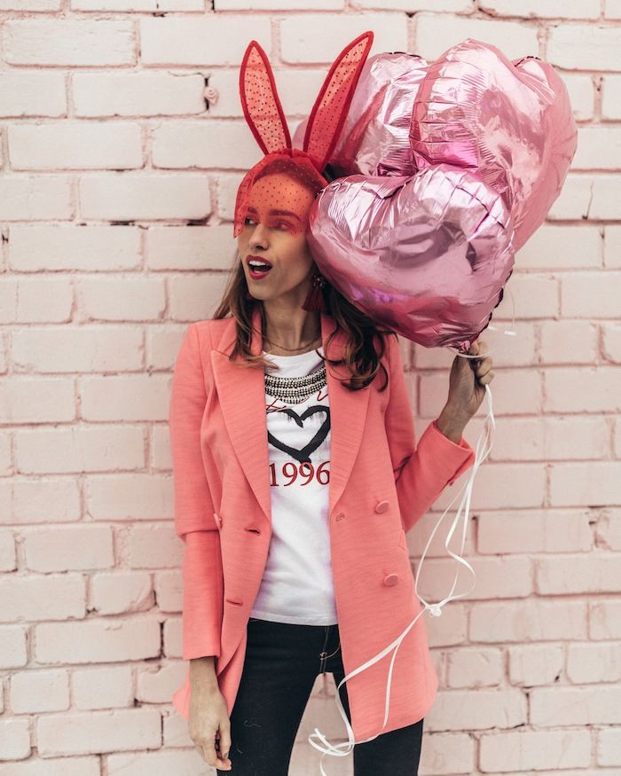 woman holding a bunch of pink, heart shaped balloons, valentines dress, wearing white t shirt and jeans, pink blazer