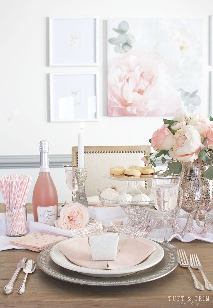 valentine's day decoration ideas, dinner table set for two, peony flower bouquet in the middle, cake stand and champagne