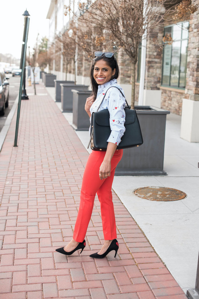 woman walking on the sidewalk, wearing red pants, blue shirt and sunglasses, black bag and shoes, valentines dress