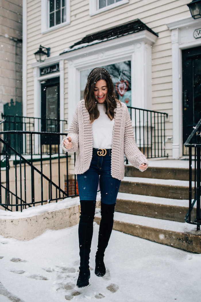 woman standing in the snow, valentines outfits, wearing white blouse and cardigan and jeans, black velvet knee high boots