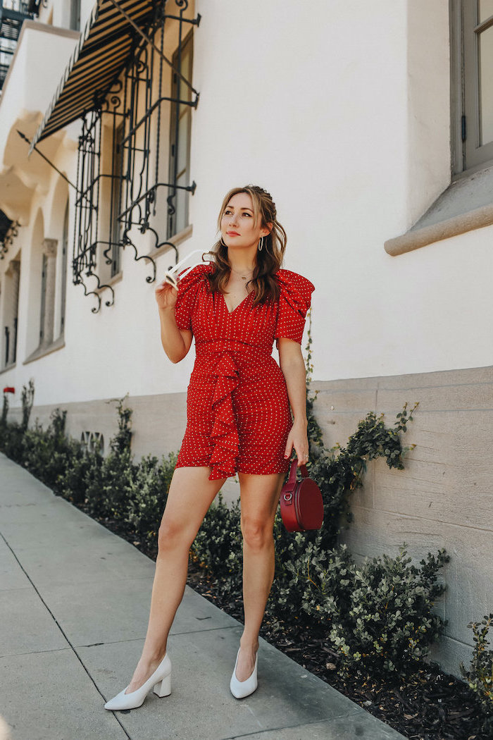woman standing on sidewalk, wearing short red dress, white shoes and red bag, valentines outfits, white sunglasses