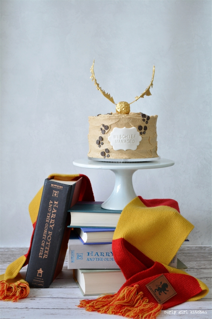 happee birthdae, one tier cake covered with buttercream, mischief managed, placed on cake stand on top of books