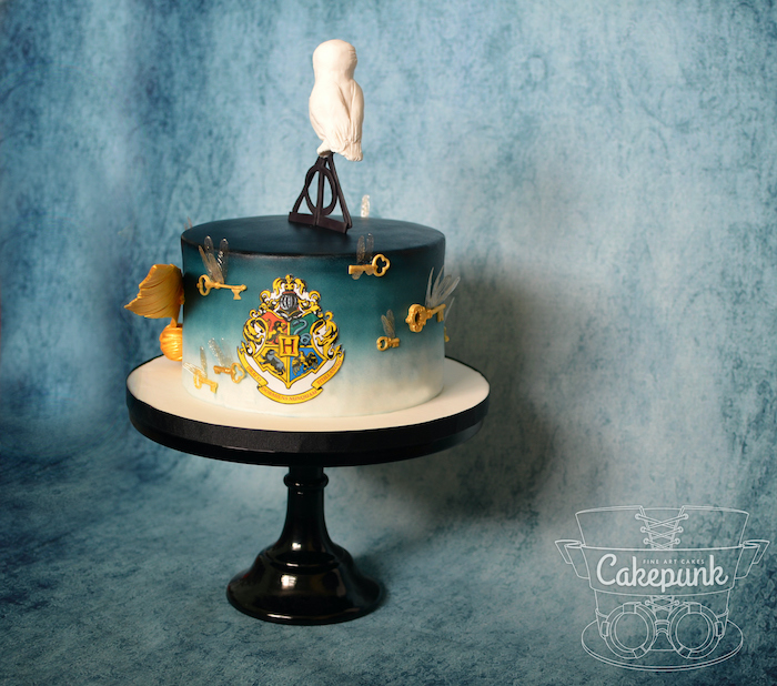cake covered with blue and white fondant, placed on black cake stand, happee birthdae, deathly hallows symbol and hedwig on top