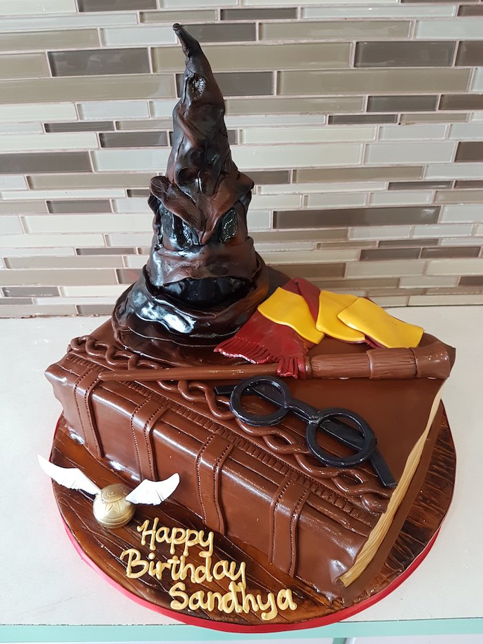 one tier cake in the shape of a book, happee birthdae, sorting hat and wand, gryffindor scarf and glasses on top