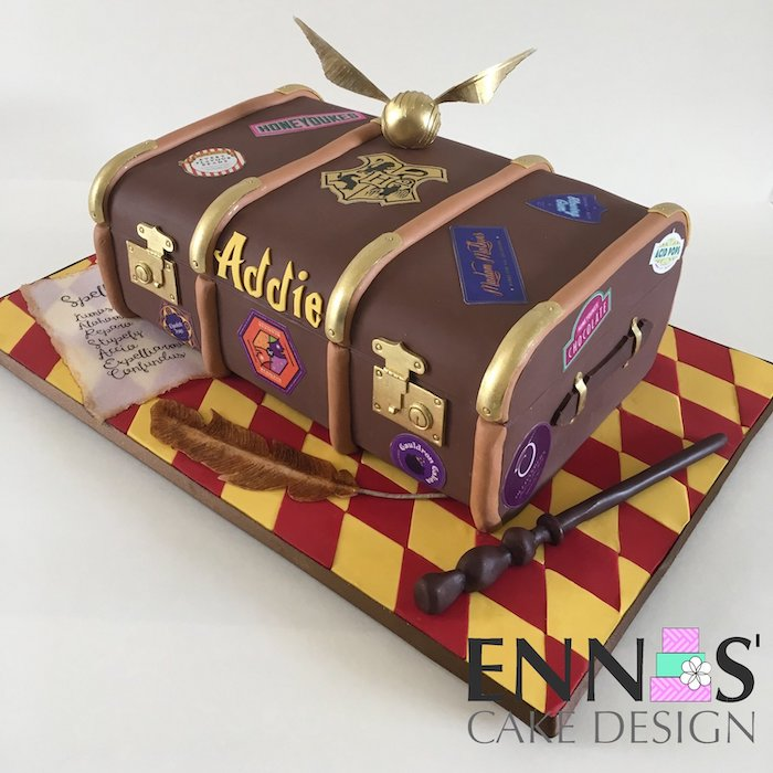 cake in the shape of a trunk, covered with brown fondant, happee birthdae, golden snitch on top, wand on the side