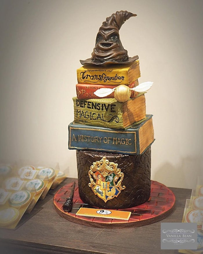 happy birthday harry cake, layers of cake in the shape of books, sorting hat made of fondant on top, placed on wooden table