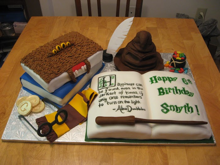 cakes in the shape of different books, arranged on silver tray, happy birthday harry cake, gryffindor scarf and sorting hat