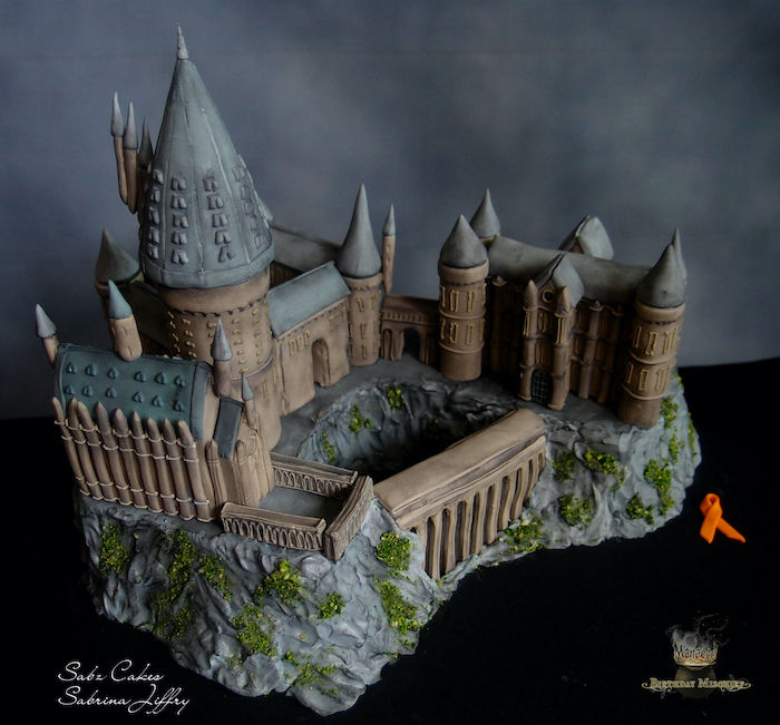 large cake in the shape of the whole hogwarts castle, happy birthday harry cake, made with fondant, placed on black surface