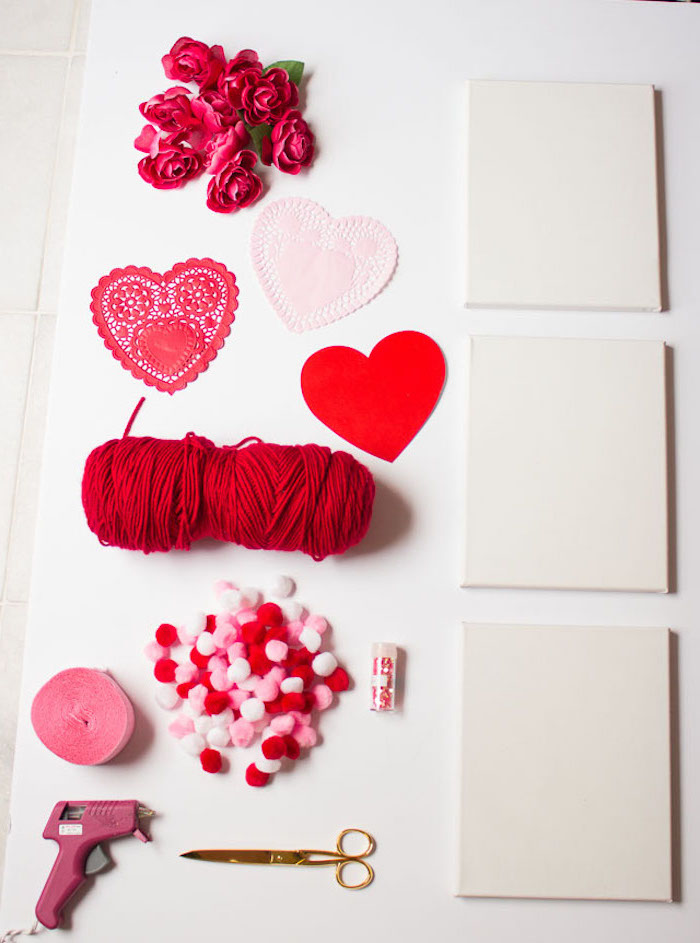 step by step diy tutorial, valentine decorations, white canvases, pom poms and yarn, faux flowers and hearts for decoration