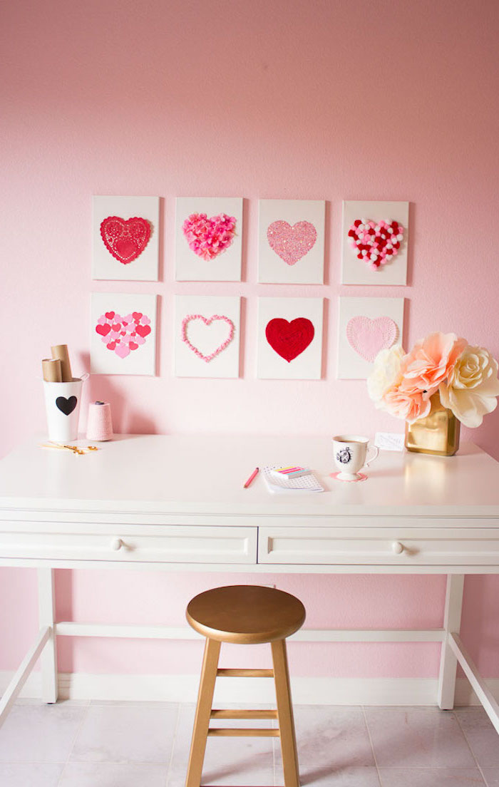 valentine decorations, eight canvases with different hearts portrayed on them, hanging on pink wall, over a white desk