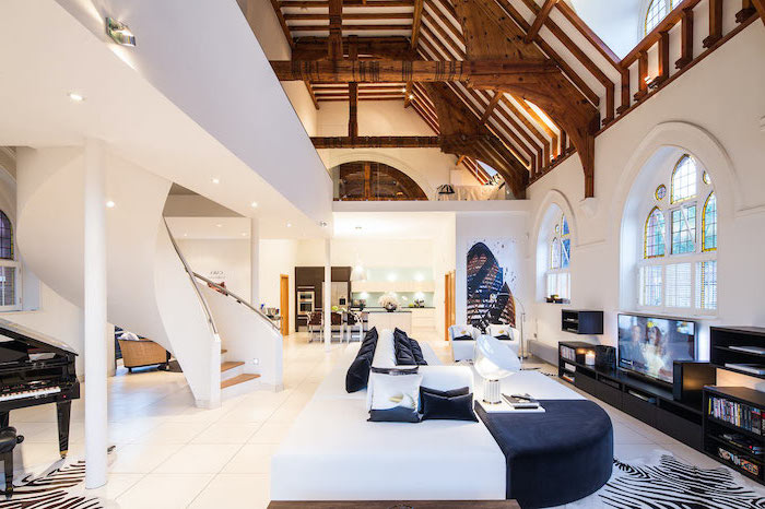 large two storey house with cathedral ceiling, stained glass panels, black and white sofa, large staircase and white tiled floor
