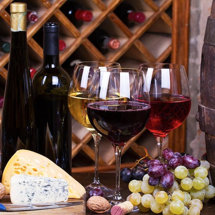 wine bottles and wine glasses, cheese and grapes, placed on wooden table, good valentines day gifts for her, wine tasting