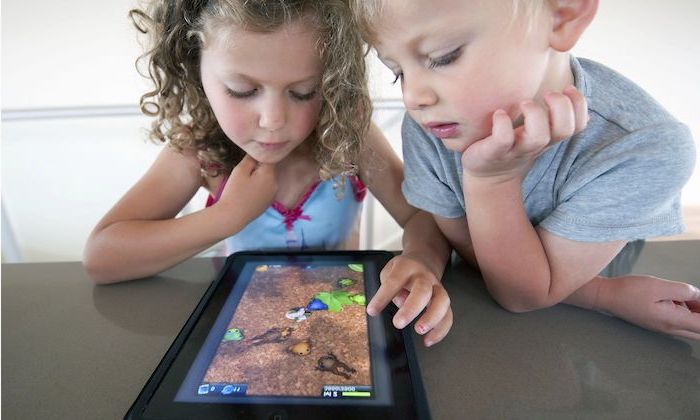 children's games, little boy and girl leaning on a grey surface, playing games on a tablet