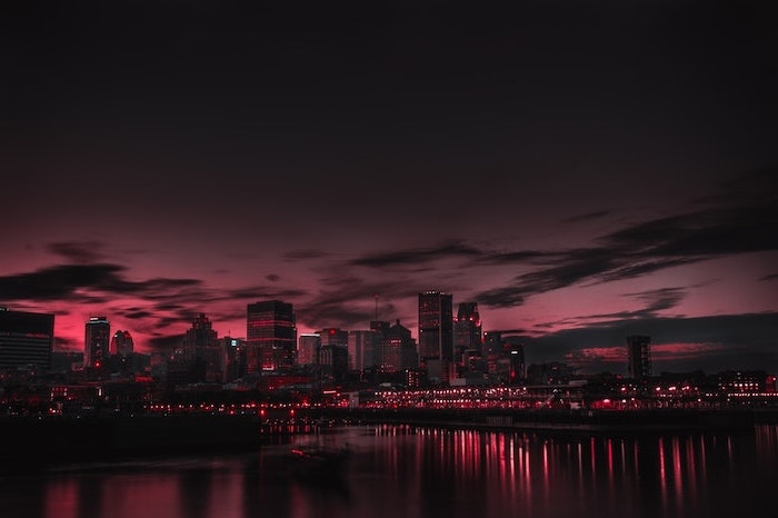 city skyline, photographed just after sunset, aesthetic desktop wallpaper, lights illuminated in the ocean