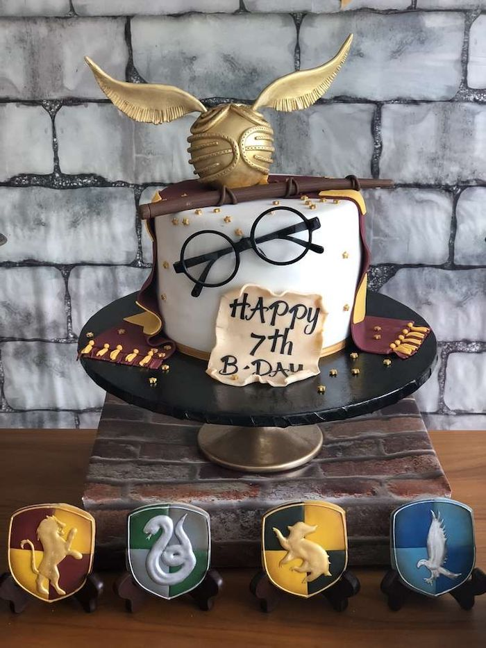 one tier cake, covered with white fondant, golden snitch on top, happy birthday harry cake, cookies with each hogwarts house symbol