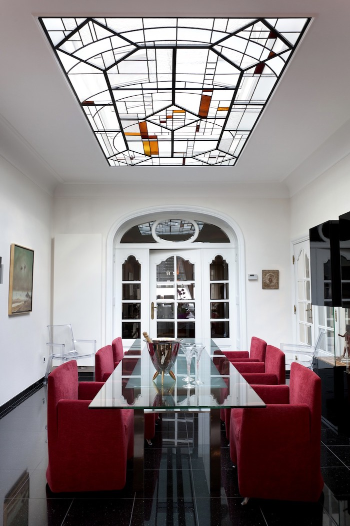 stained glass windows, large ceiling window, above a glass dining table, red chairs around it, arranged on black tiled floor