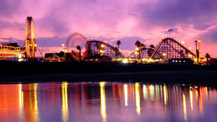 amusement park on a pier, photographed at sunset, aesthetic desktop wallpaper, lights illuminated in the ocean