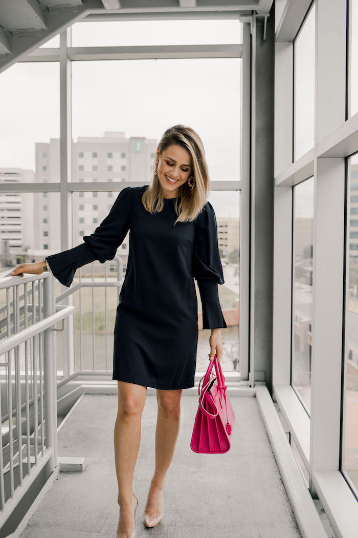 woman wearing black dress with long sleeves, pink leather bag, nude shoes, red dress for valentine's day