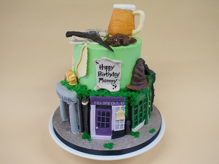 two tier cake with green fondant, diagon alley shops on the bottom tier, harry potter cake hagrid, butterbeer on top