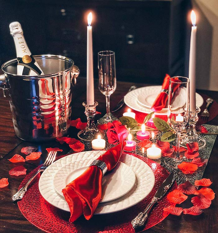 dinner table set for two, red napkins and rose petals, candles and candlesticks on it, valentine's day decoration ideas