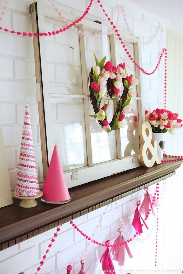 heart shaped wreath made with tulips, valentine's day decoration ideas, pink garlands hanging over white mantel