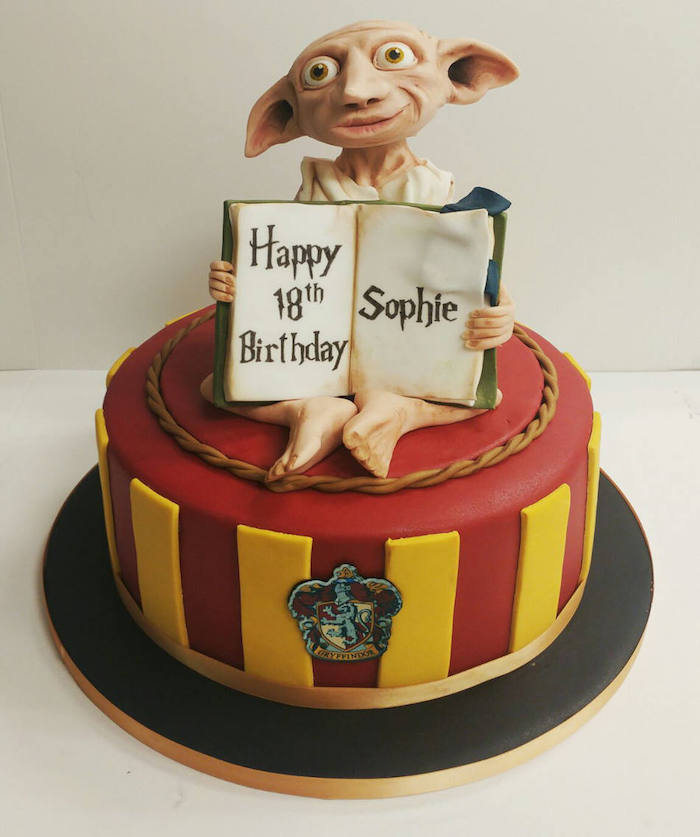 one tier gryffindor cake with red and yellow fondant, harry potter cake hagrid, dobby made of fondant on top