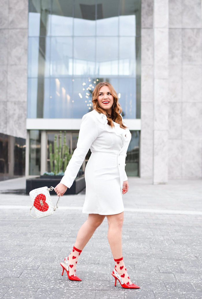 woman smiling, walking on sidewalk, red dress for valentine's day, wearing white dress with long sleeves, red heels with socks with hearts